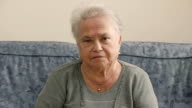 old depressed woman sit on the sofa stares at the camera video