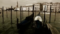 Old film effect footage of the Venetian gondolas rocking on the waves in front of Piazza San Marco video