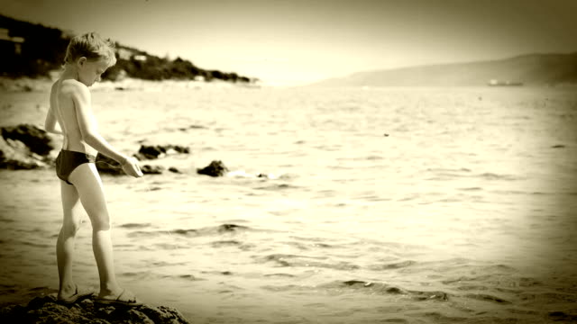 Old film effect: young fisherman trying to catch himself a crop with a fishing line. video