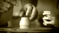 Old film footage: agedcraftsman's hands creating a piece of pottery teaching his little student video