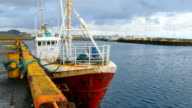 Old fishing boat is moored in Grindavik, Iceland, dock is on background, cloudy weather video