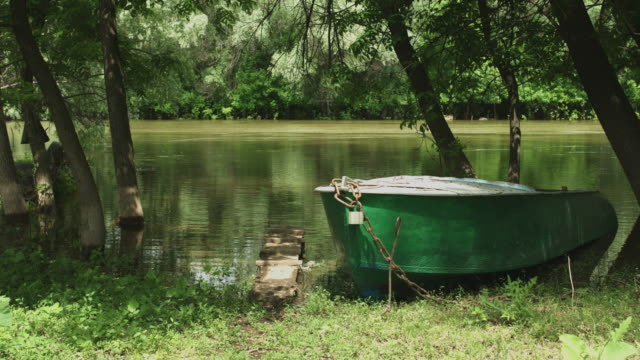 Old fishing boat on the shore of calm river video