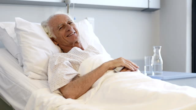 Old happy patient lying on bed video