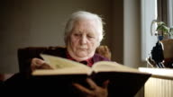 SLOW MOTION: Old human reading a book. Close up video