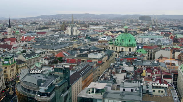 Old low-rise and modern buildings' roofs in Vienna on a cloudy day, Austria. FullHD overview pan shot video
