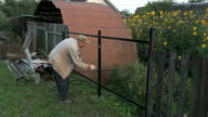 Old man 70s paints the iron fence using a black video