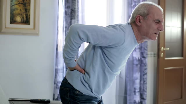 old man getting up from the sofa feeling back pain - backache video