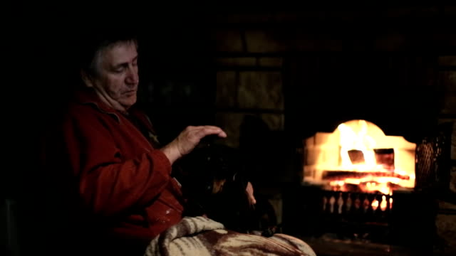 Old man petting his dog near the fireplace video