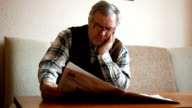 Old man reading the newspaper at home video