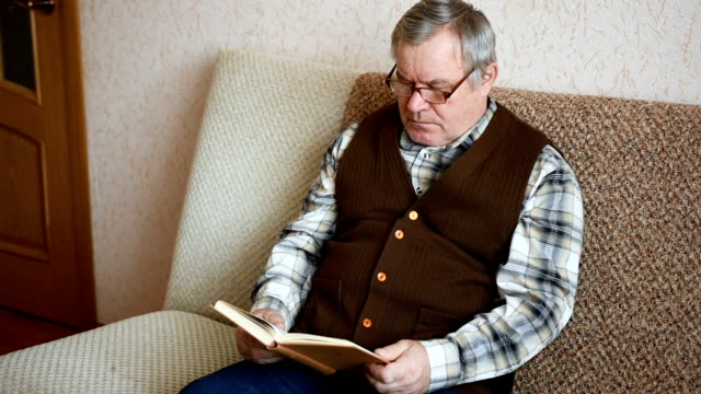 Old man sitting on the couch at home reading a book video