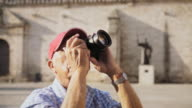 Old Man Tourist Taking Souvenir Picture With Photo Camera In Cuba video