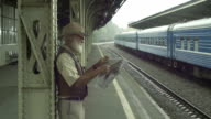 Old Man With Newspaper On Train Station video