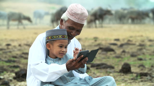 Old muslim man with little boy playing mobile phone. video
