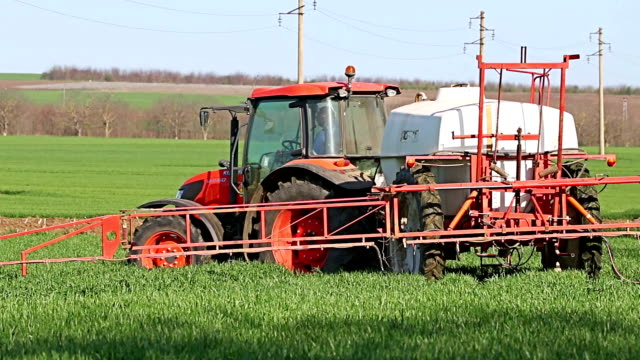 Old red Tractor spraying field, rural landscape in countryside video