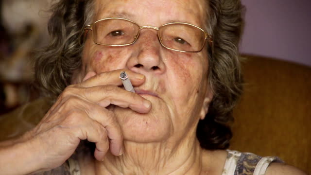 Old retired woman smoking cigarette in home video