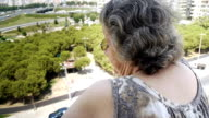 Old retired woman watching traffic from balcony video
