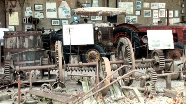 Old rusty gears, barrels, tractors in the covered warehouse video