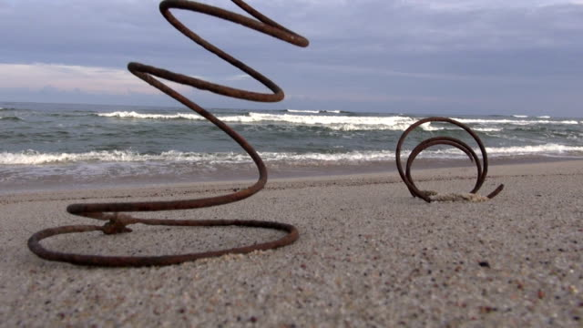 old rusty metal spring on ocean beach sand and waves video
