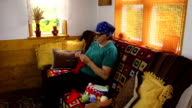 Old senior grandmother woman sit on sofa and knit stockings video