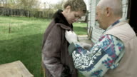 Old senior man helps young woman to clean clothes video