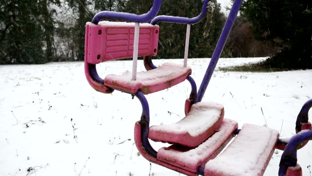 old swing outdoors with heavy snow in winter video