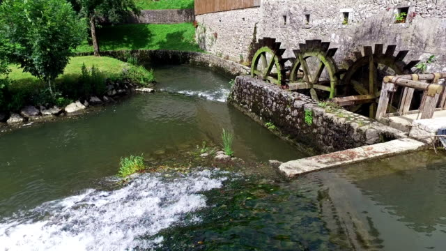 Old water mill still working. Wooden wheels of old mill are rotating near the Postojna Cave, Slovenia. video