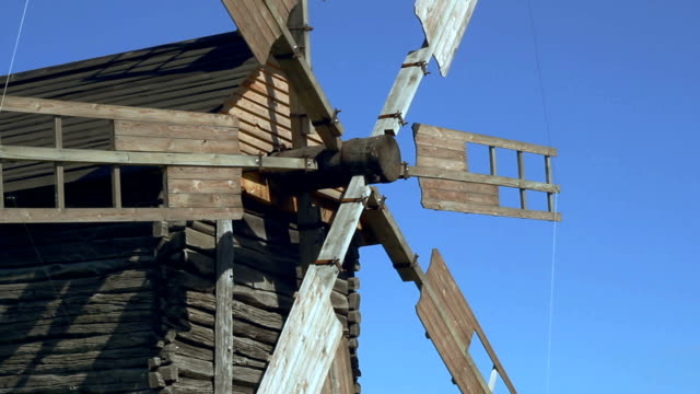 Old windmill blades rotating on wind. Wind power and traditional mill building video