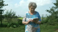Old woman 80s holding a digital tablet outdoors video