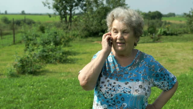 Old woman 80s telling on the smartphone outdoors video