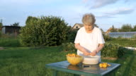 Old woman cleaning chanterelle mushrooms video