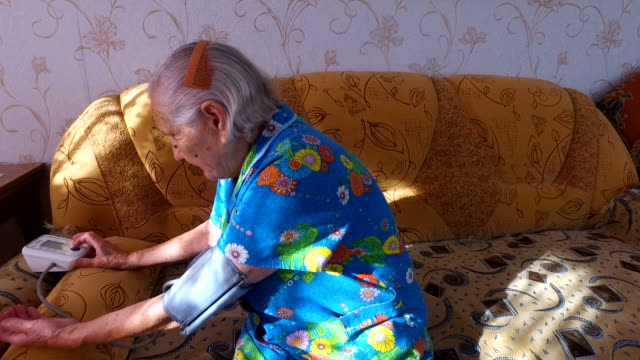 Old woman measures the blood pressure yourself. She sits on the couch in his apartment. The quiet old age. video