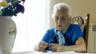 old  woman praying with rosary beads, crucified Christ, cross, elderly video