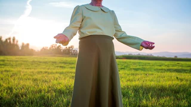Old woman raising arms in an idyllic scene video