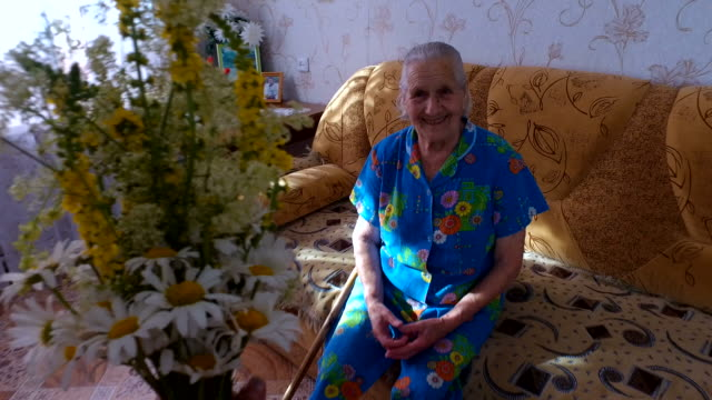 Old woman receives a bouquet of wildflowers. Woman sits on the couch in his apartment. video