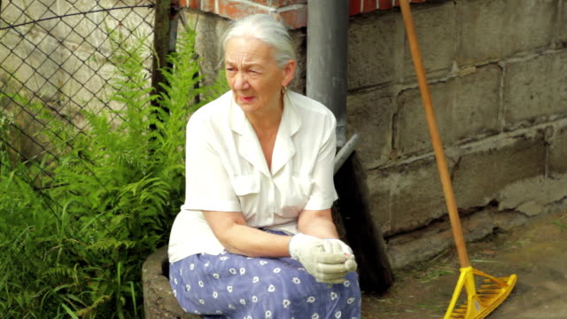 Old woman resting after work in the garden. Worries. video