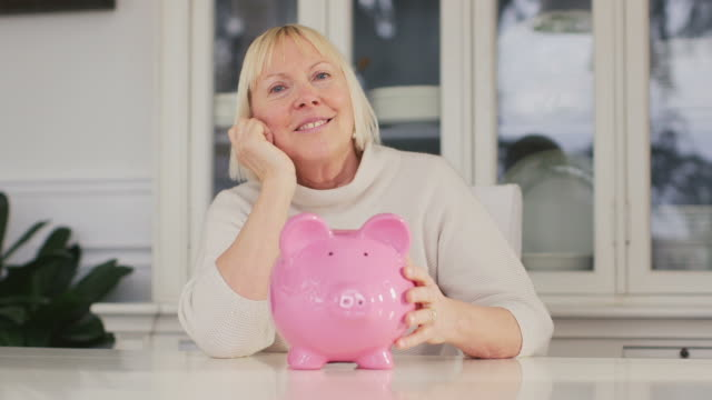 Old woman showing piggybank and euro coin video