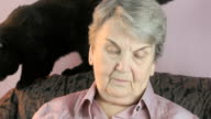 Old woman sits at a armchair next to a black cat video
