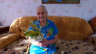 Old woman sitting on a couch in his apartment. She holds flowers in hands video