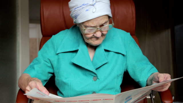 old woman sitting on chair and reading newspaper video