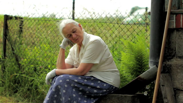 Old woman sitting, resting. Portrait of mother or grandmother. video