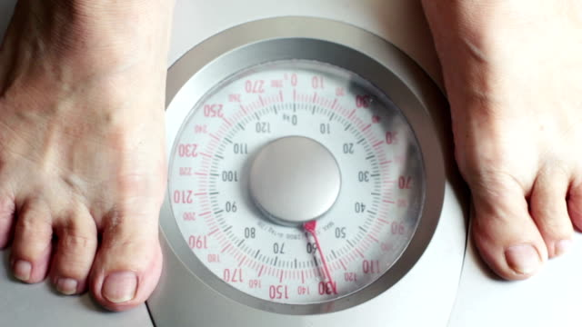 Old woman stepping on weight scale video