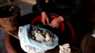 old woman strip off the silkworm cocoon for silk in traditonal way. video