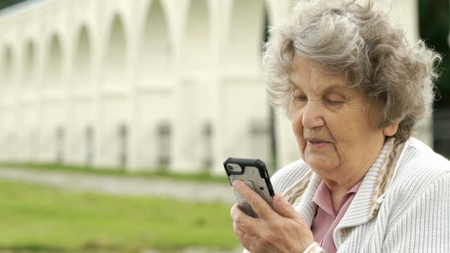 Old woman talking with a friend using a smartphone video