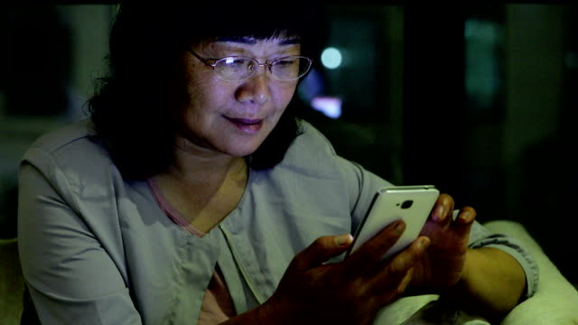 Old woman using mobile phone at home video