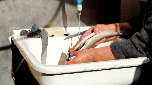 Old woman washes fish. video