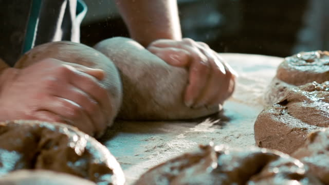 Old women in tradition clothes kneading dough on table. Slowly video
