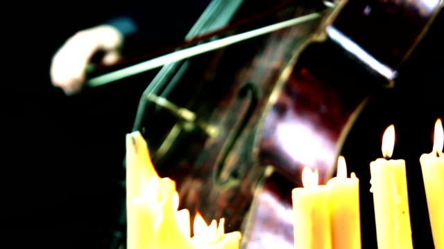 old wooden cello playing in a candles light video