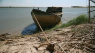 Old wooden dredging barge tied on the riverbank video