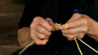 Old wrinkled farmers hands knitting video