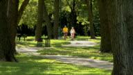 Older couple biking through the park video